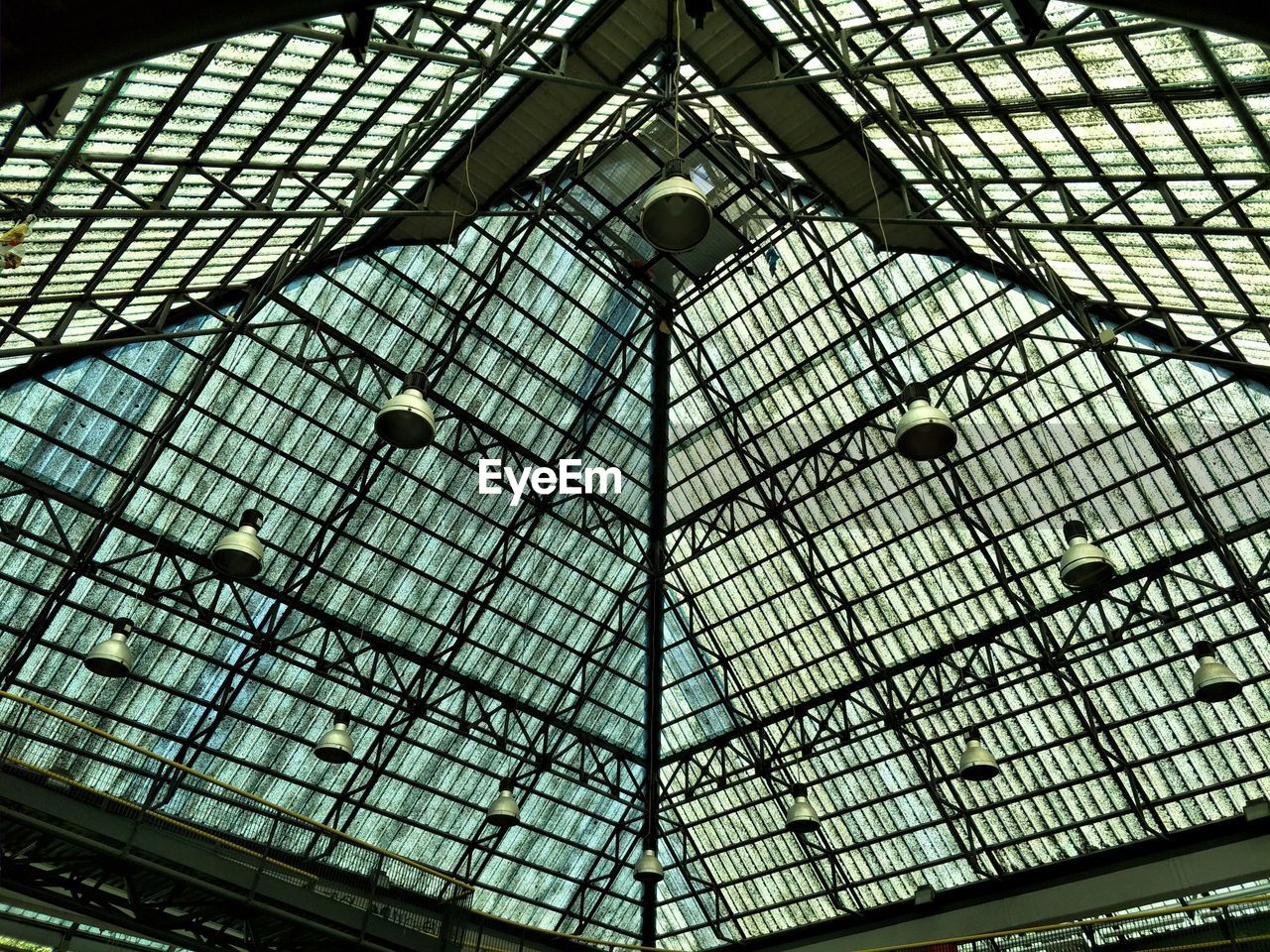 low angle view, architecture, built structure, ceiling, indoors, pattern, no people, glass - material, day, building, sunlight, design, transparent, dome, skylight, architectural feature, glass, roof, architecture and art