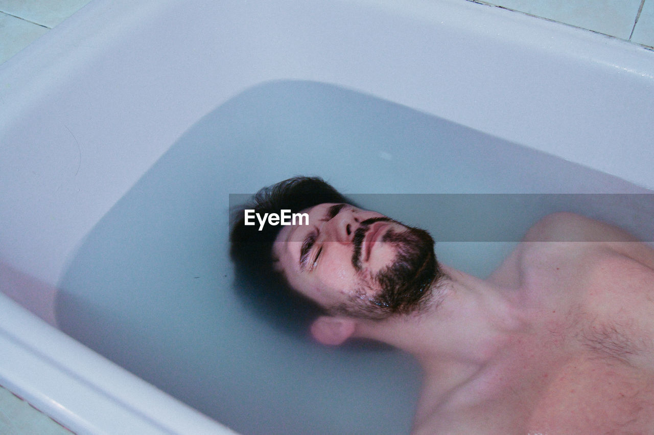 Close-Up Of Man Lying In Bathtub
