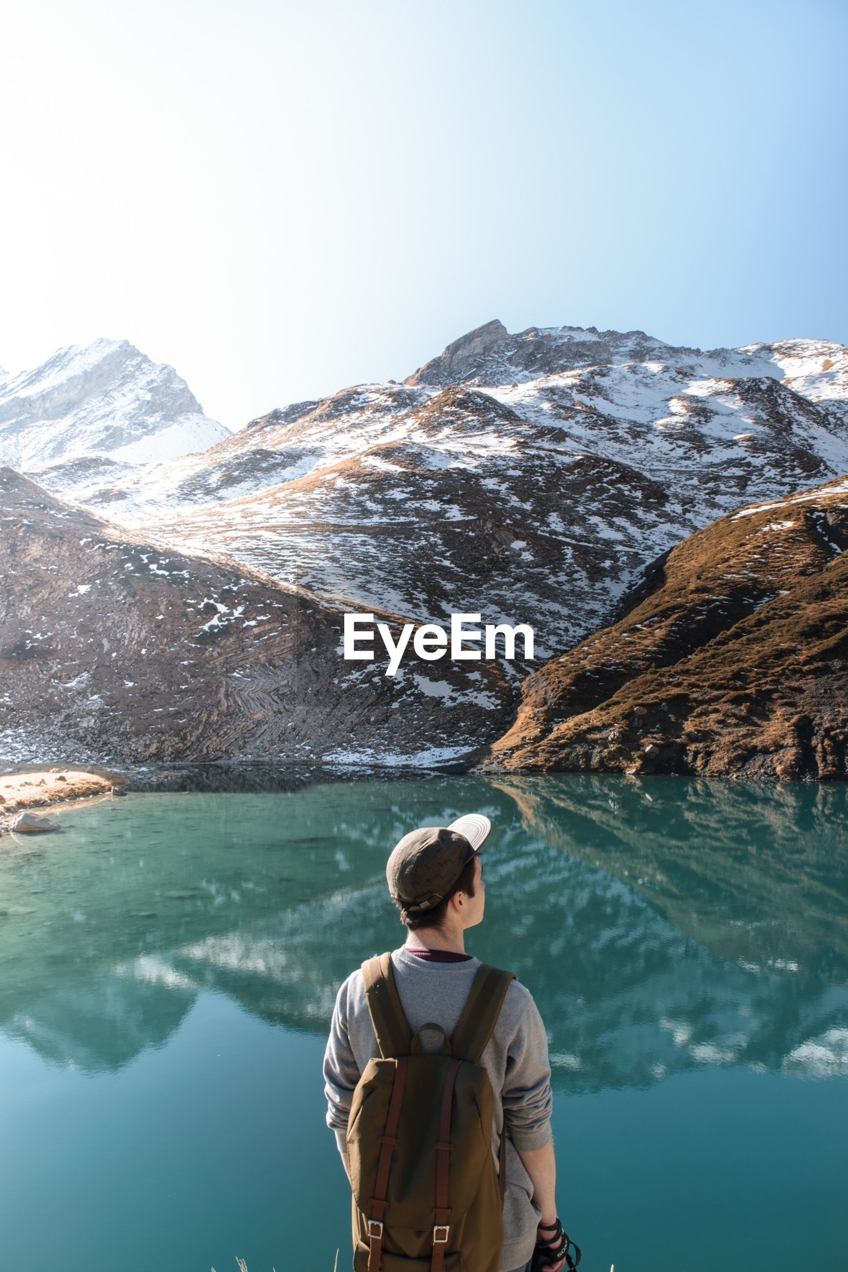 mountain, water, lifestyles, leisure activity, scenics, mountain range, beauty in nature, winter, standing, clear sky, rear view, tranquil scene, tranquility, lake, nature, cold temperature, casual clothing, waist up