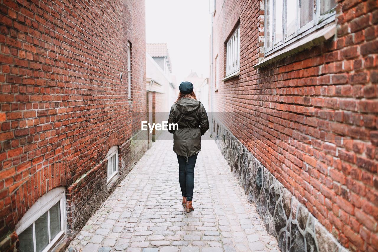 Full length of woman walking in alley amidst buildings