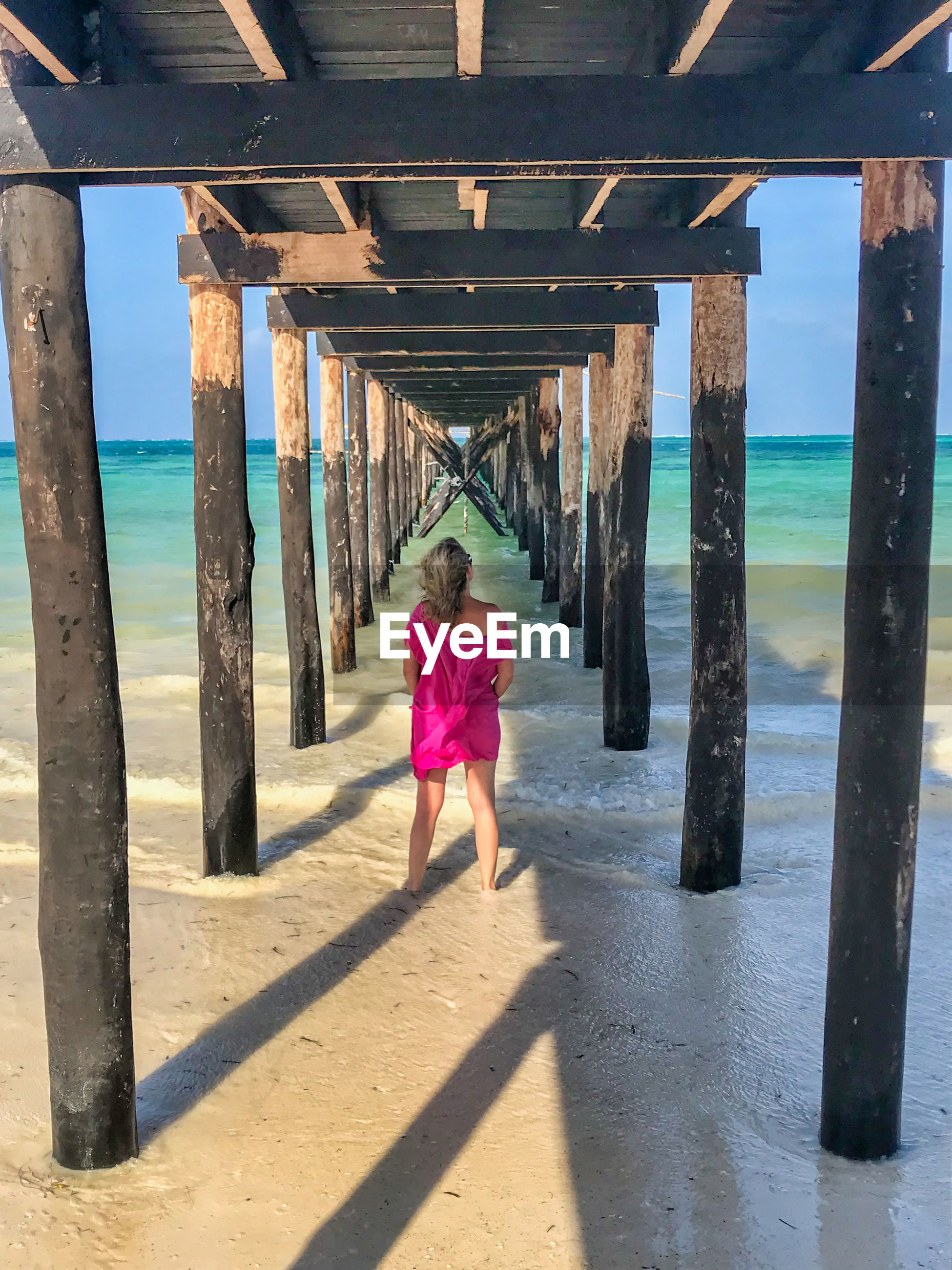 Rear view of woman standing below pier at beach