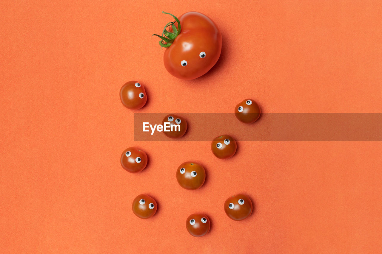 indoors, red, no people, still life, large group of objects, orange color, representation, copy space, close-up, food, studio shot, high angle view, colored background, food and drink, fruit, freshness, human representation, tomato, art and craft, toy, orange background