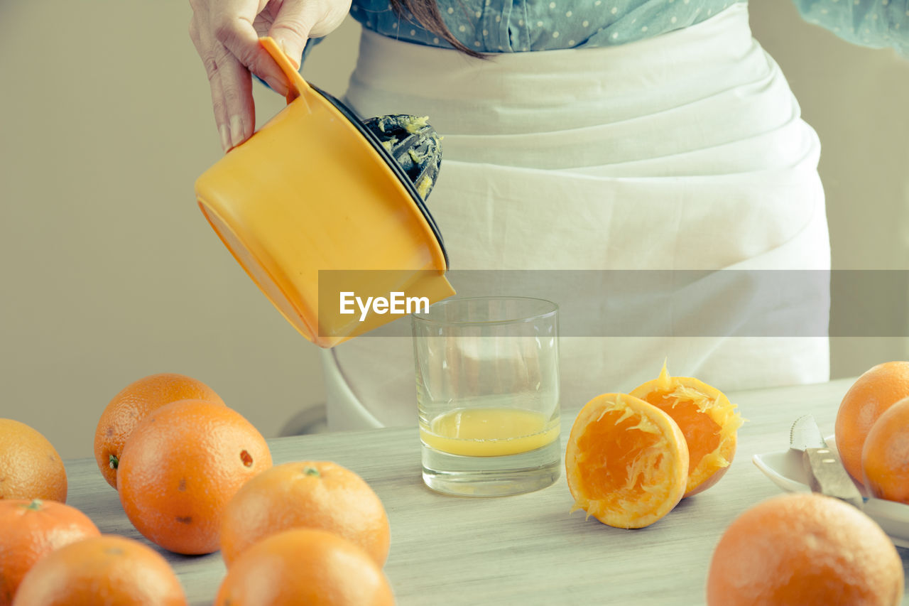 Midsection of woman pouring juice of orange on table