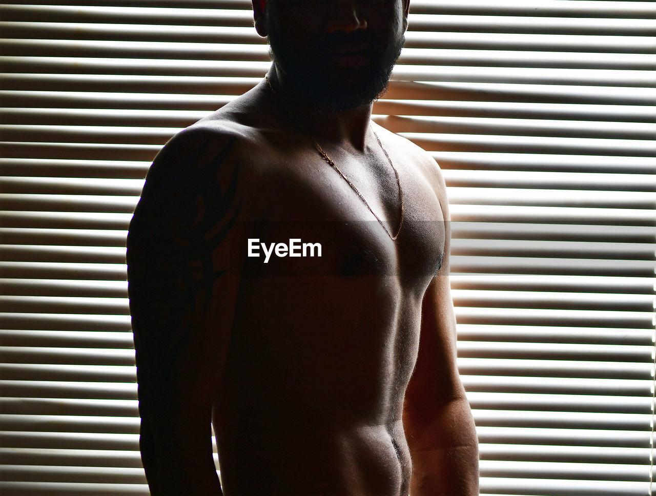 Shirtless Man Standing Against Window