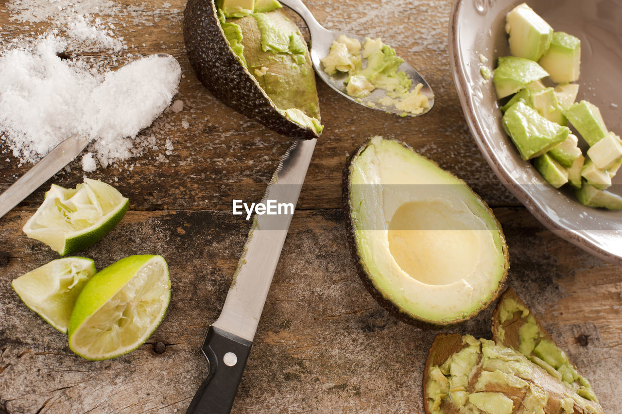 High Angle View Of Knife And Halved Avocado On Wooden Table