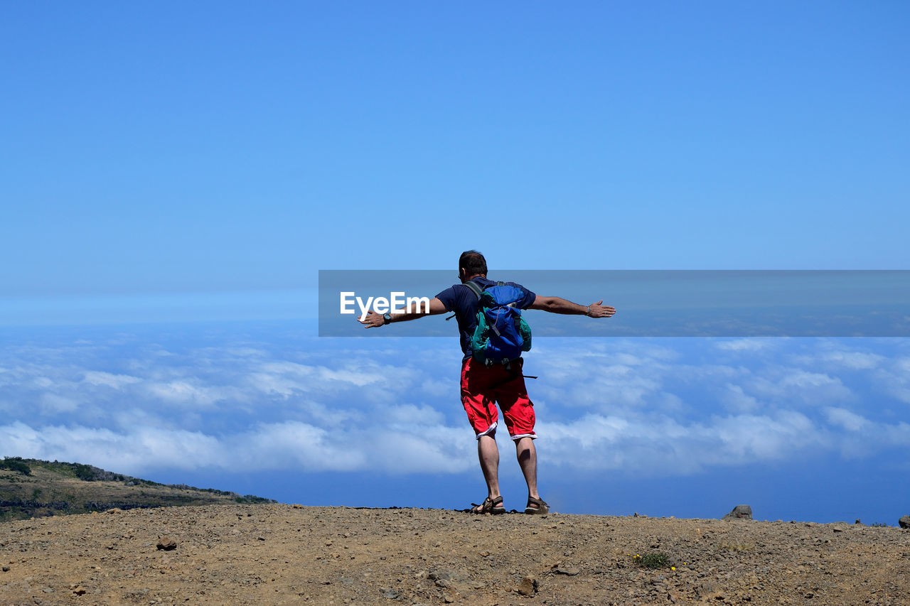 Man With Arms Outstretched On Hillside