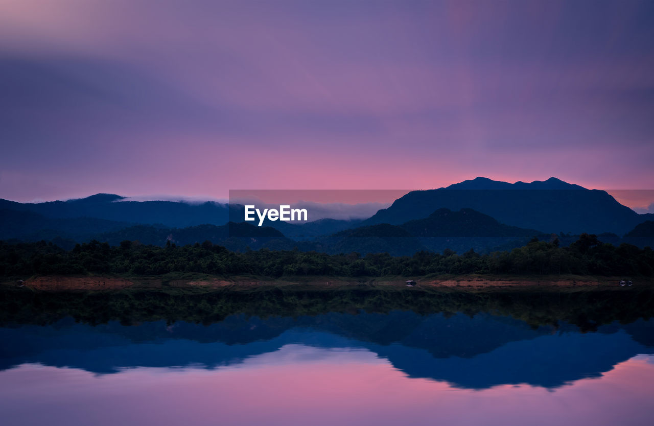 Scenic view of lake by silhouette mountains against romantic sky