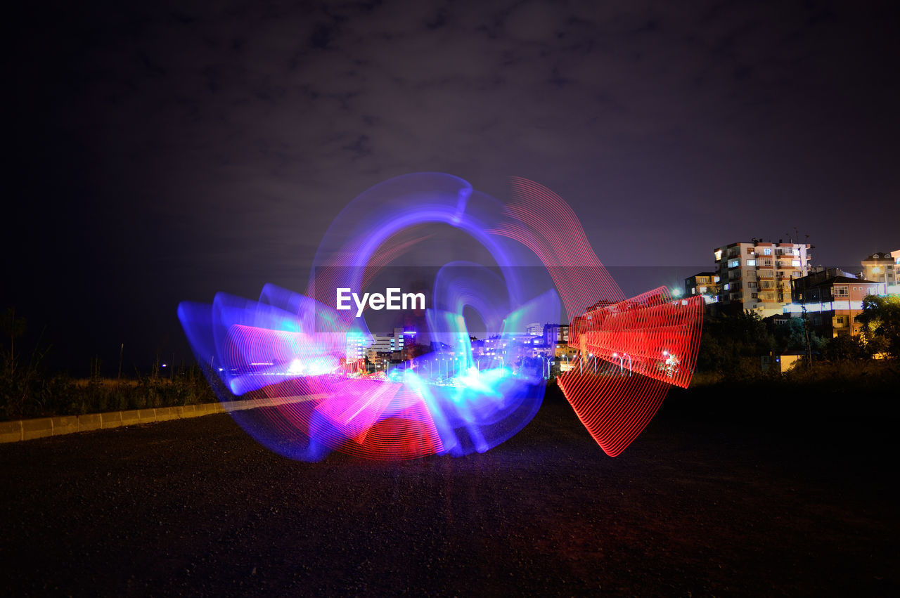 DIGITAL COMPOSITE IMAGE OF ILLUMINATED LIGHT TRAILS IN CITY AGAINST SKY