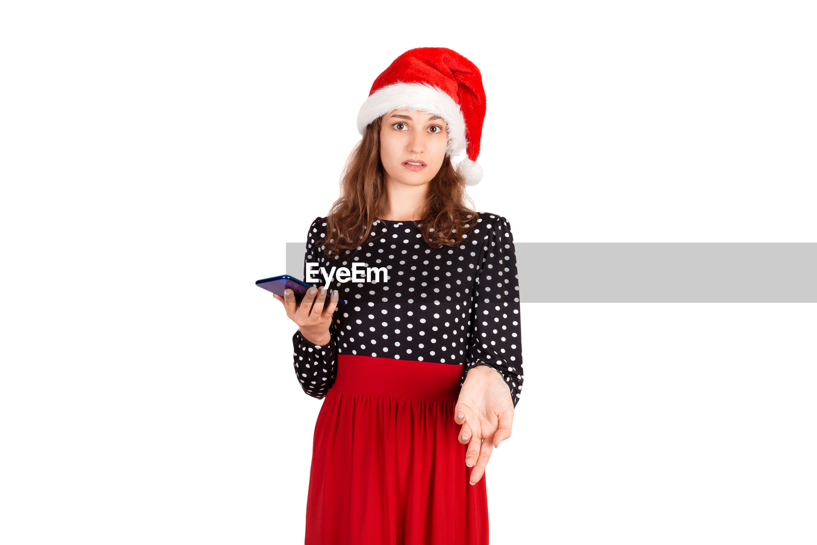 Portrait of beautiful young woman holding mobile phone while standing against white background