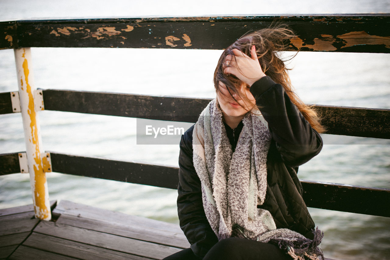 Thoughtful Young Woman With Hand In Hair Sitting On Pier Over Sea