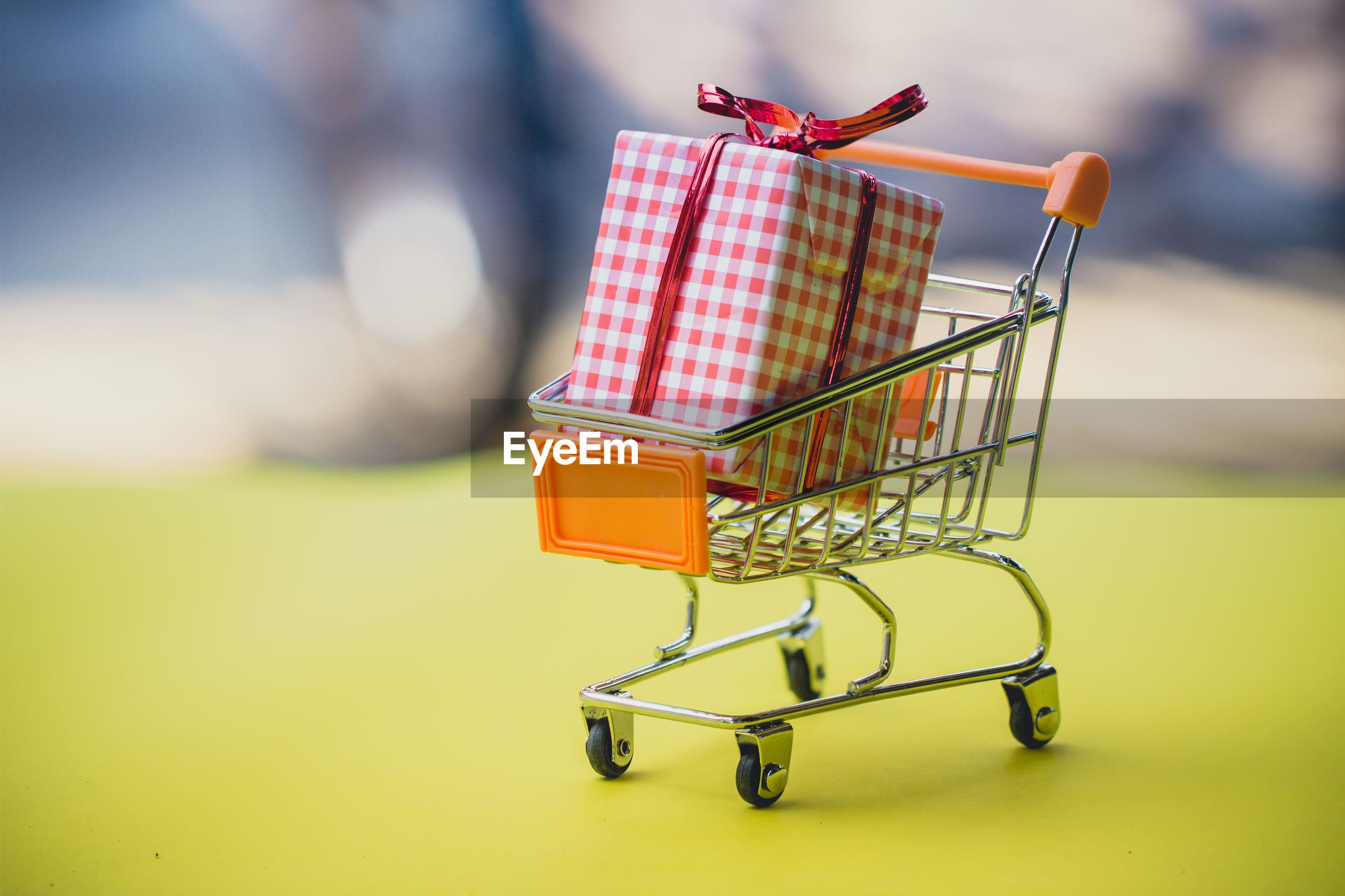 Close-up of shopping cart with gift box on table