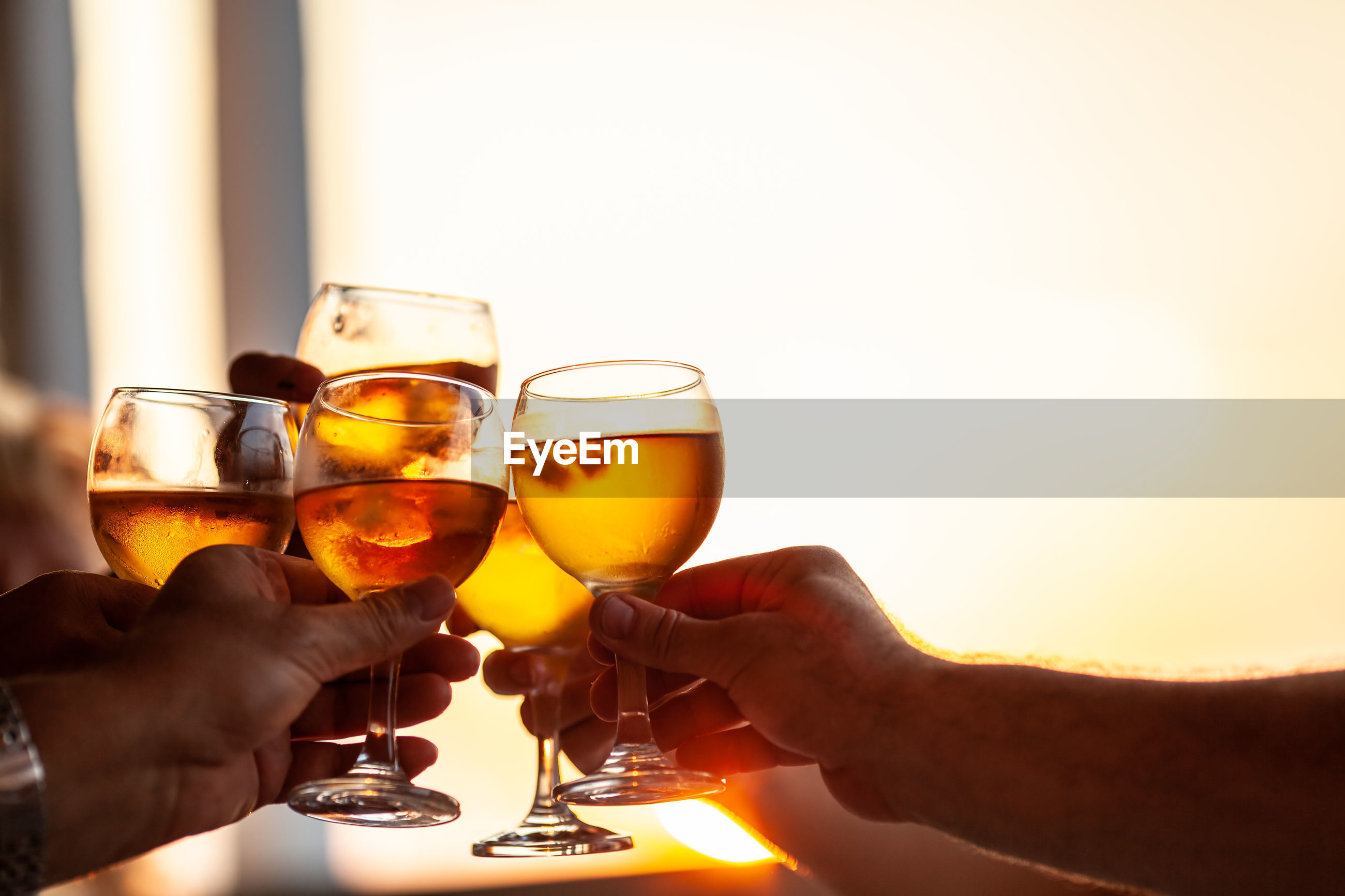 MIDSECTION OF MAN HOLDING DRINK WITH GLASS