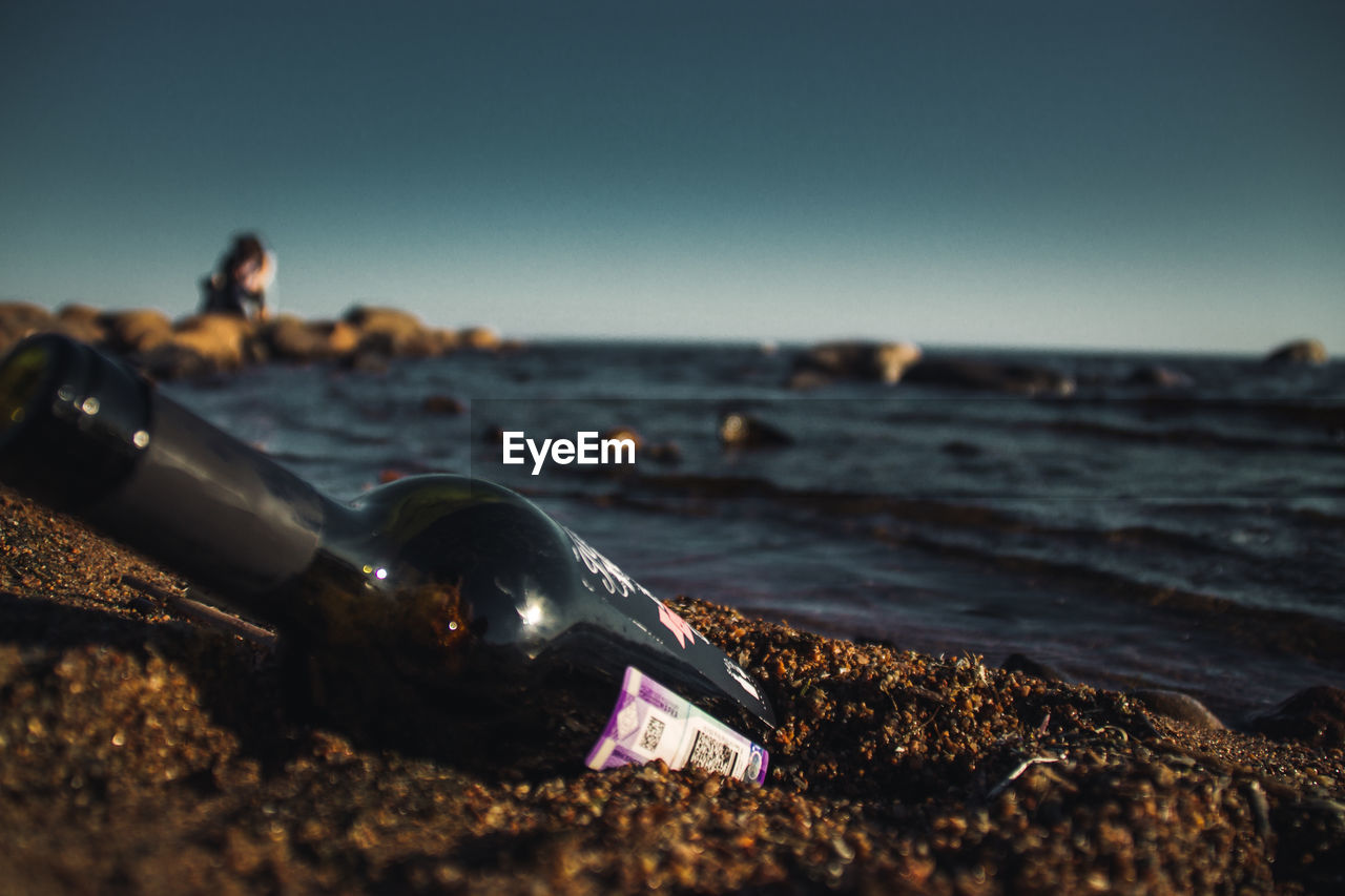 sea, water, beach, sky, land, nature, bottle, clear sky, day, horizon over water, solid, horizon, rock, beauty in nature, scenics - nature, focus on foreground, outdoors, selective focus, container, pollution, pebble