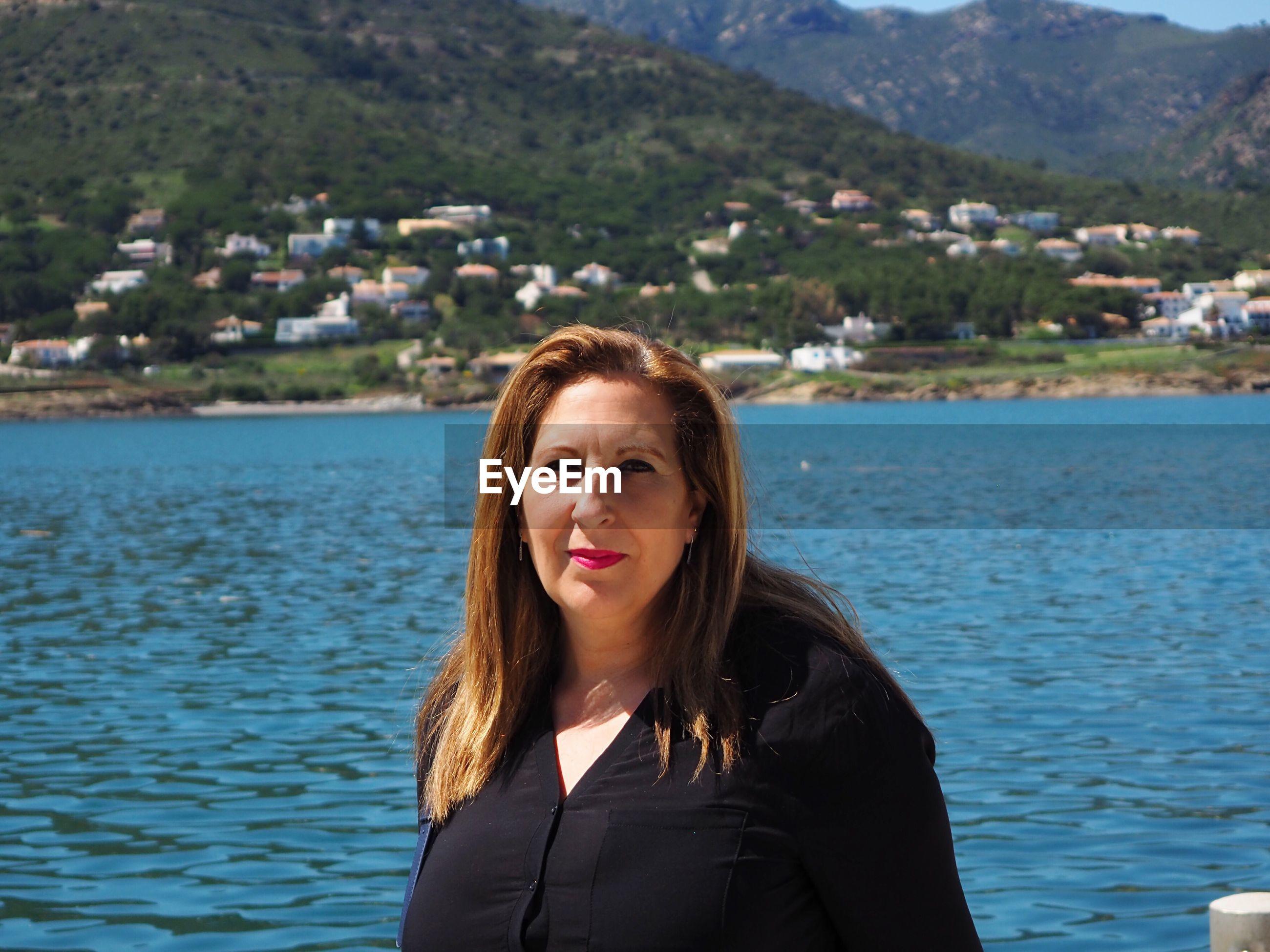 Portrait of woman against river