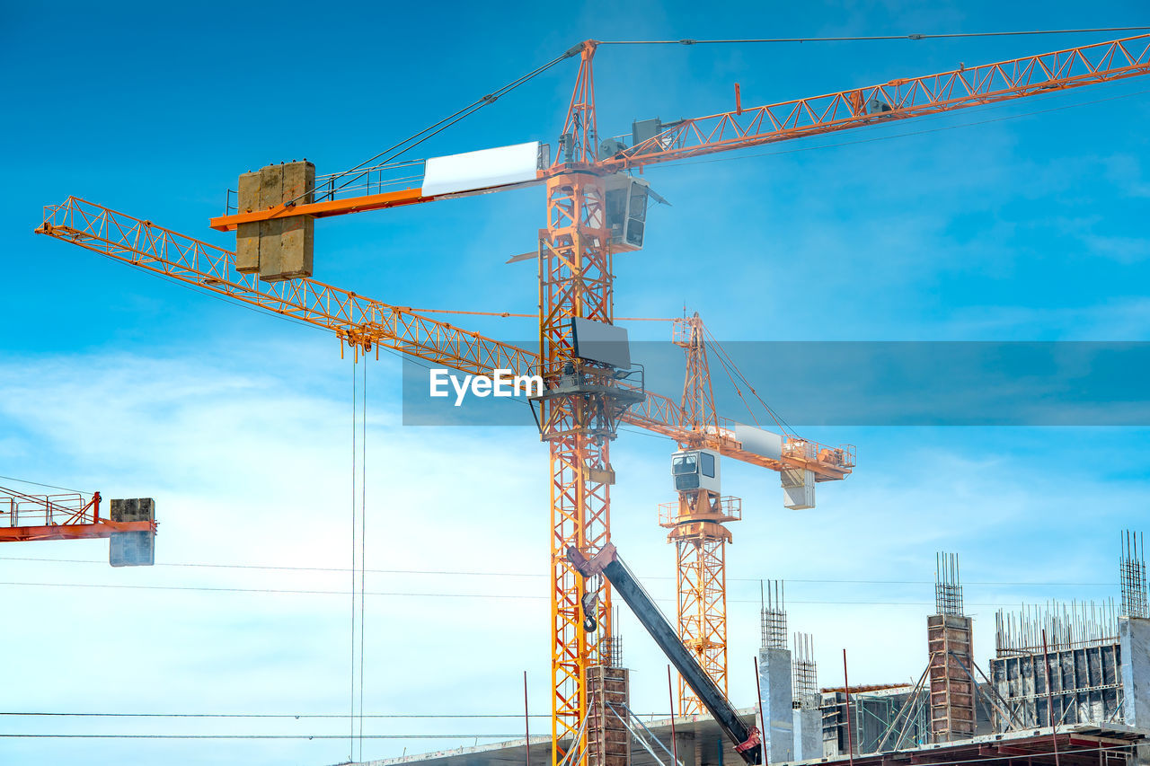 crane - construction machinery, architecture, built structure, sky, industry, construction industry, machinery, construction site, development, building exterior, incomplete, nature, no people, cloud - sky, metal, city, tall - high, day, low angle view, construction machinery, outdoors, modern, construction equipment