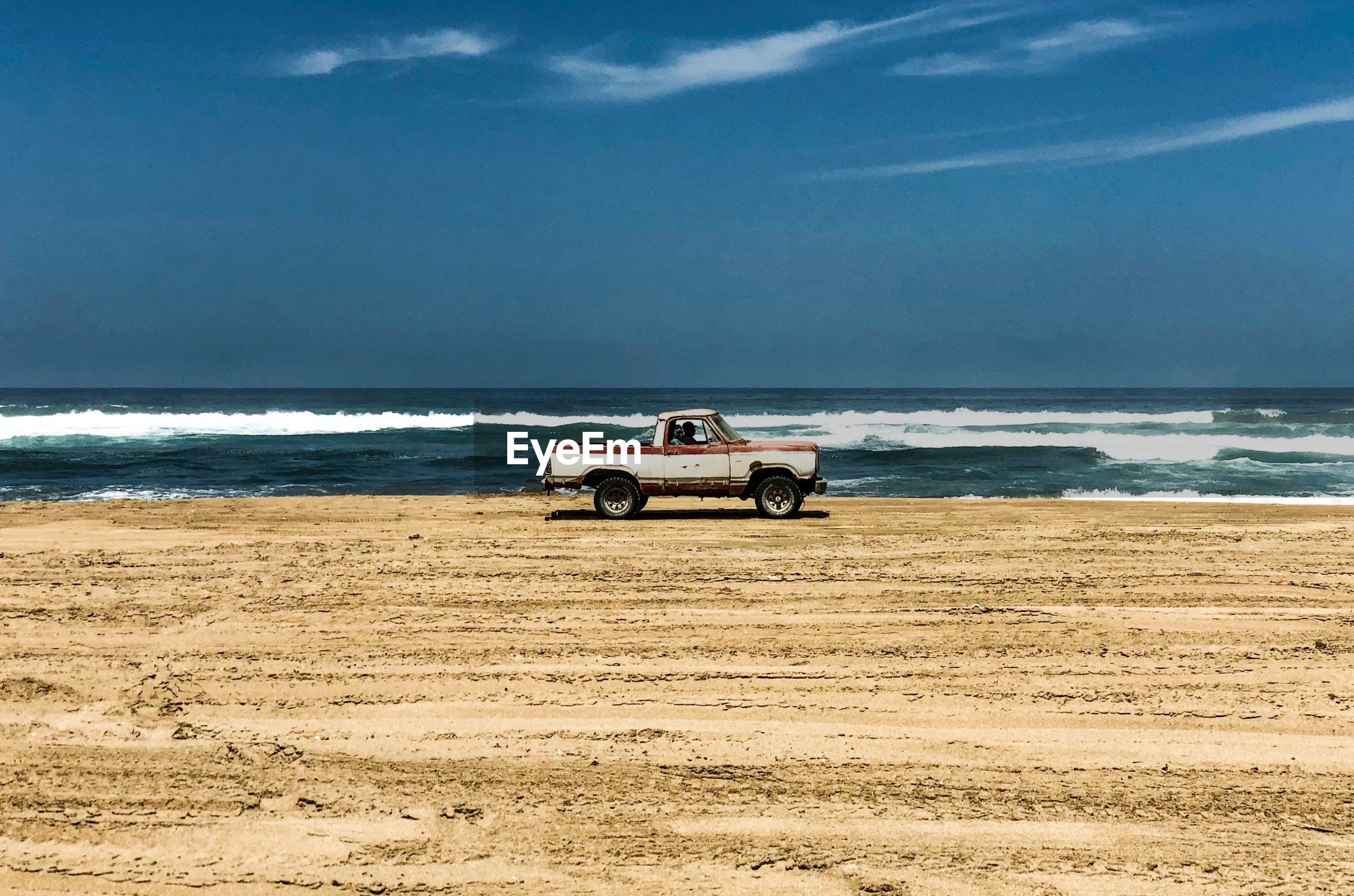 Pick-up truck moving on beach against blue sky during sunny day
