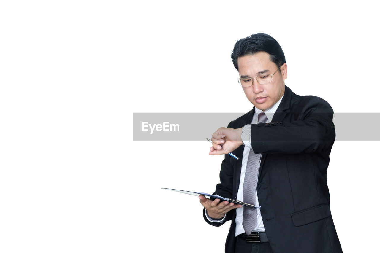 Businessman checking time while standing against white background