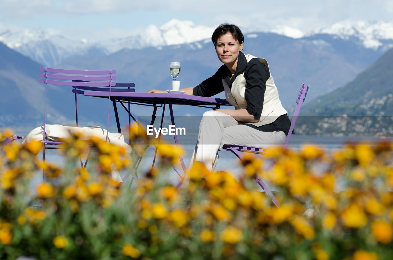 Portrait Of Smiling Mature Woman Sitting On Chair Against Lake