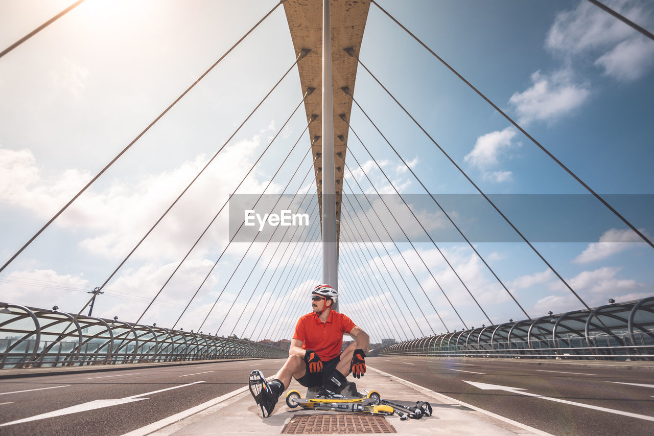 Man Sitting With Push Scooter On Bridge Against Cloudy Sky