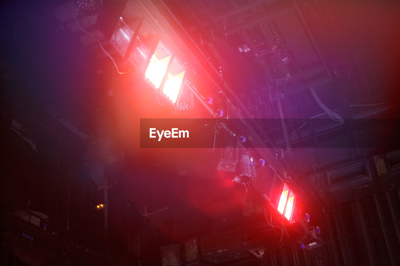 illuminated, night, red, architecture, built structure, lighting equipment, no people, building exterior, nightlife, smoke - physical structure, lens flare, accidents and disasters, low angle view, arts culture and entertainment, light - natural phenomenon, city, sign, outdoors, light beam, occupation, stage, concert