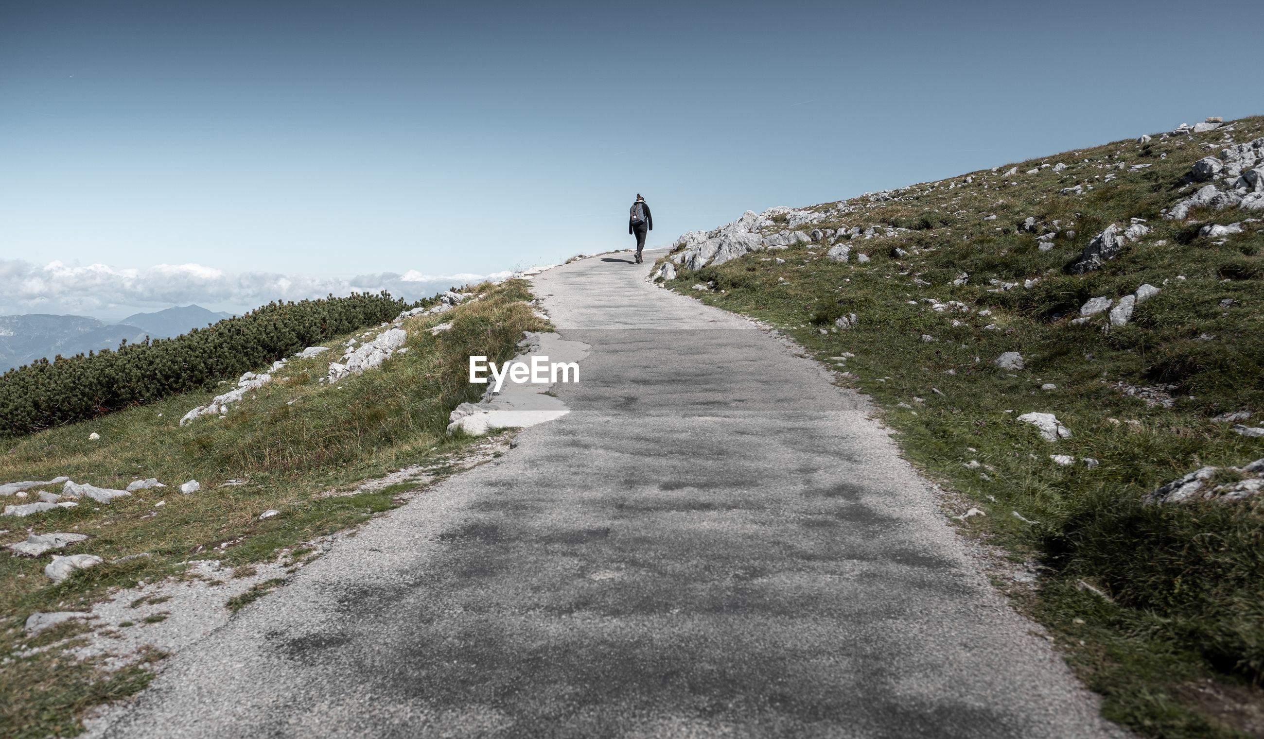 Rear view of woman walking on road on hill against sky