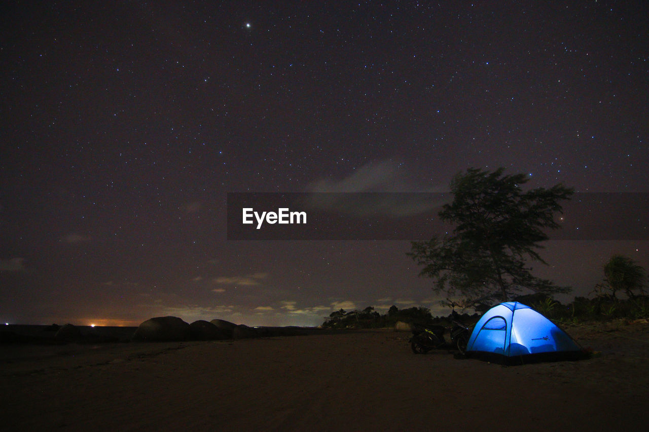 night, sky, star - space, tent, scenics - nature, space, camping, tree, nature, land, astronomy, beauty in nature, star, no people, illuminated, tranquility, blue, plant, tranquil scene, field, outdoors, milky way