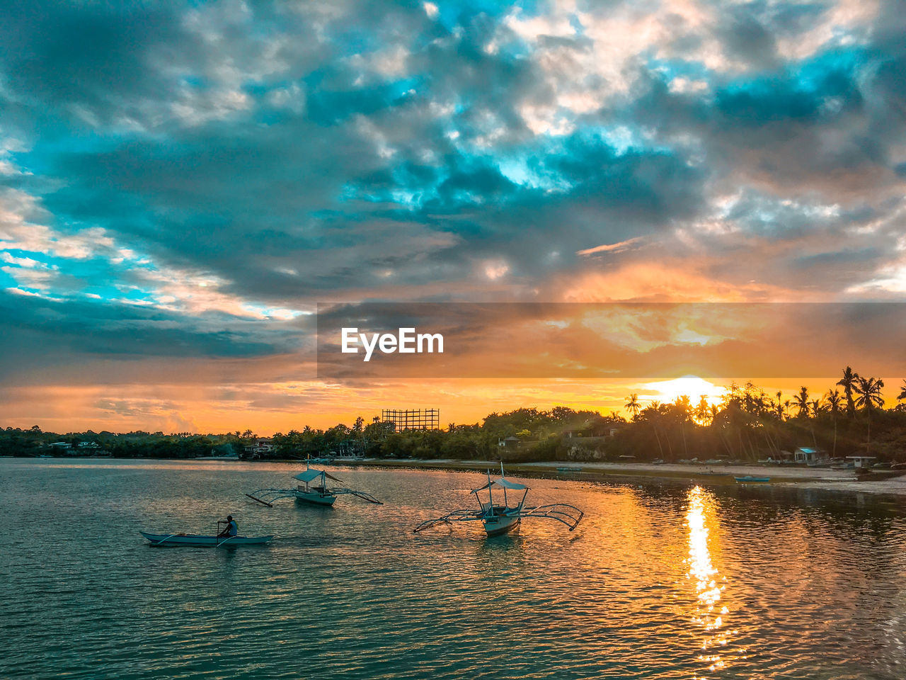 cloud - sky, sky, nautical vessel, water, sunset, transportation, mode of transportation, waterfront, beauty in nature, scenics - nature, orange color, nature, real people, tranquility, men, tranquil scene, outdoors, leisure activity, river