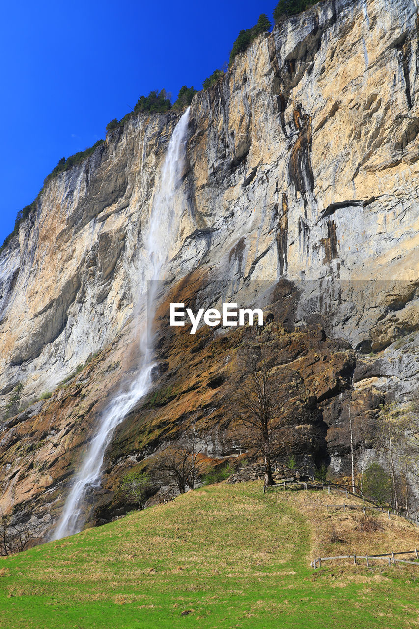 scenics, waterfall, rock - object, nature, beauty in nature, day, outdoors, no people, motion, water, tranquility, mountain, low angle view, cliff, power in nature, grass, sky