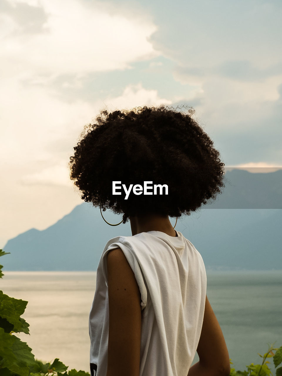 Rear View Of Afro Woman Looking At Lake During Sunset