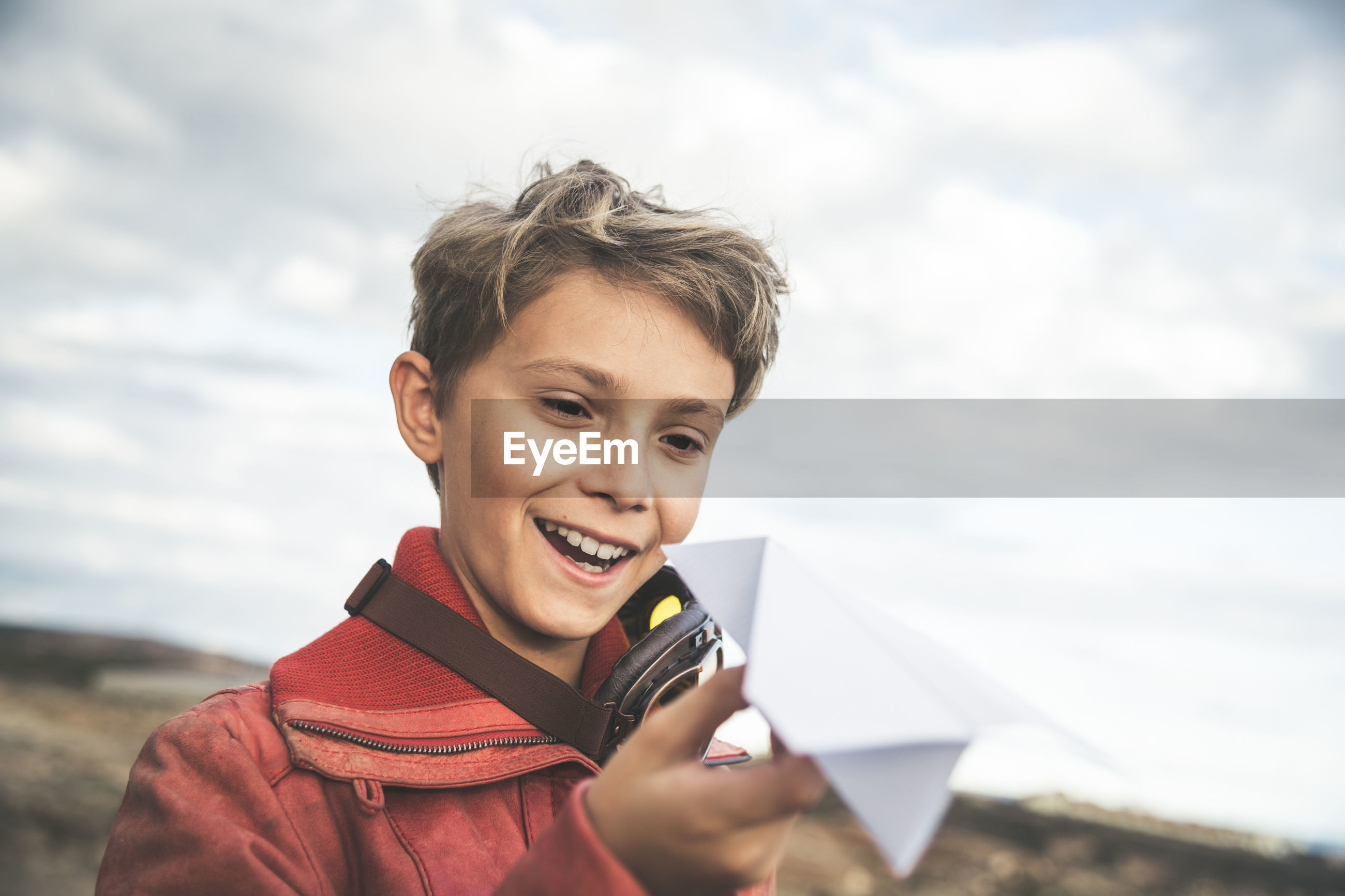Smiling boy holding paper airplane while standing against cloudy sky