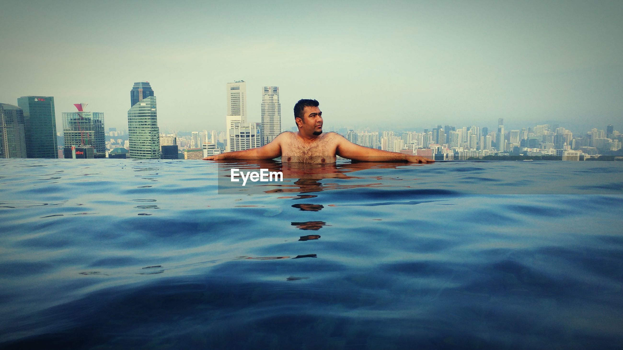 Man in swimming pool against cityscape