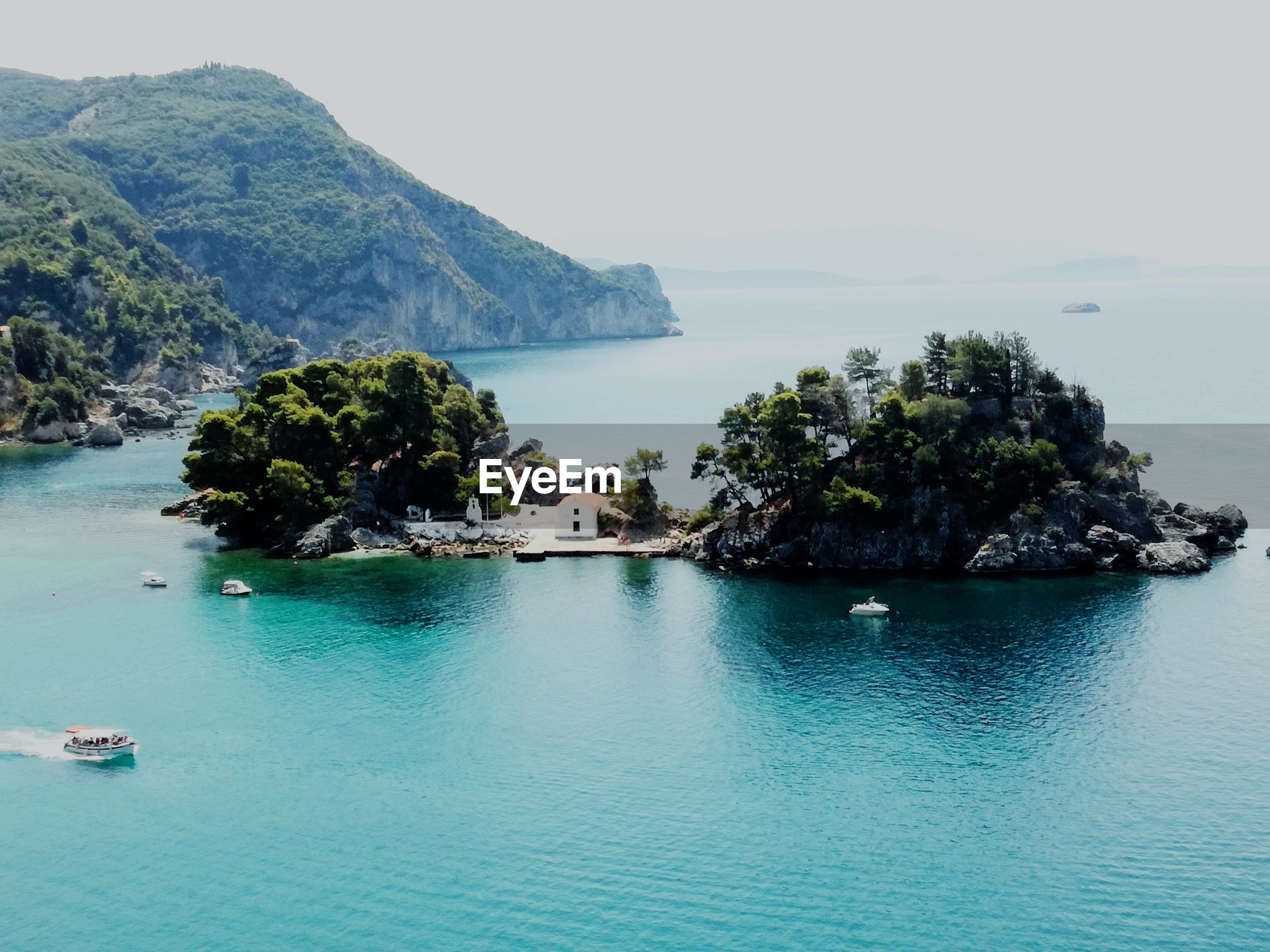 sea, scenics, water, beauty in nature, tranquil scene, nature, tranquility, mountain, idyllic, waterfront, rock - object, day, outdoors, no people, sky, horizon over water, clear sky, tree