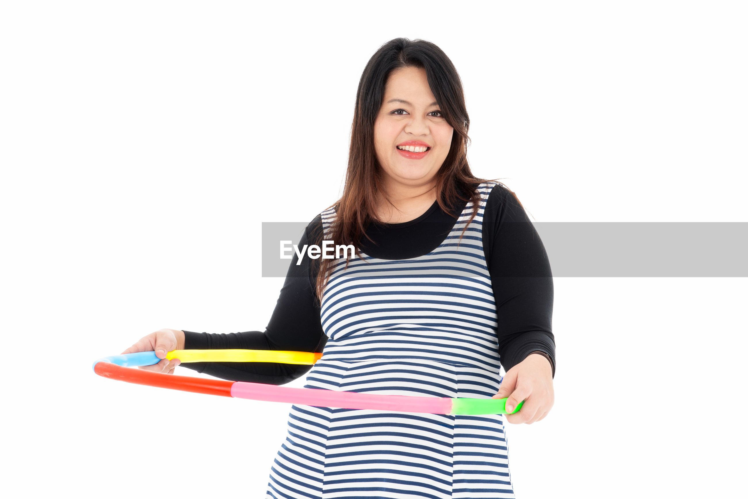 Portrait of smiling woman holding plastic hoop while standing against white background
