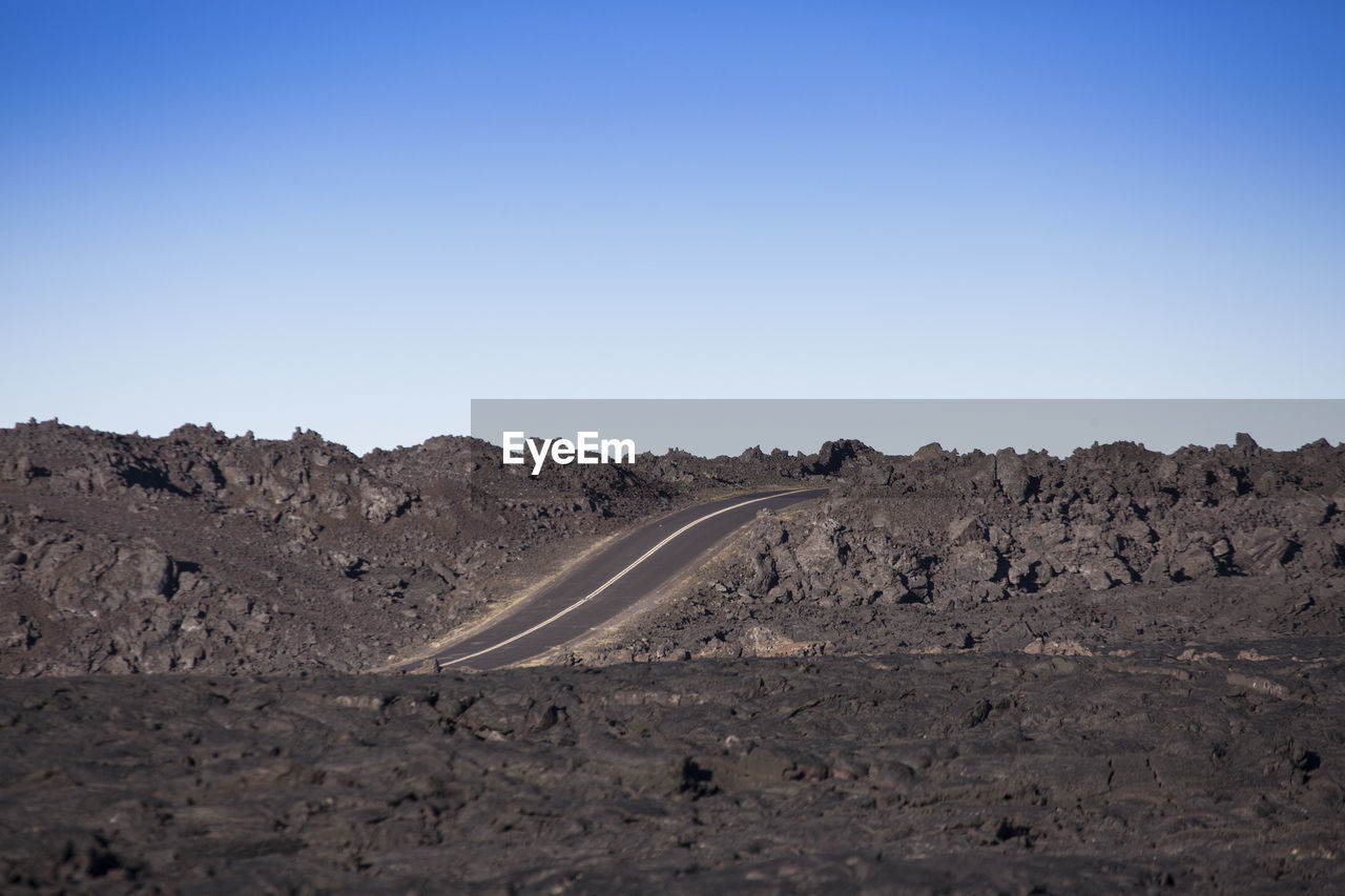 clear sky, transportation, nature, copy space, tranquil scene, landscape, no people, road, day, scenics, outdoors, blue, beauty in nature, mountain, arid climate, winding road, sky