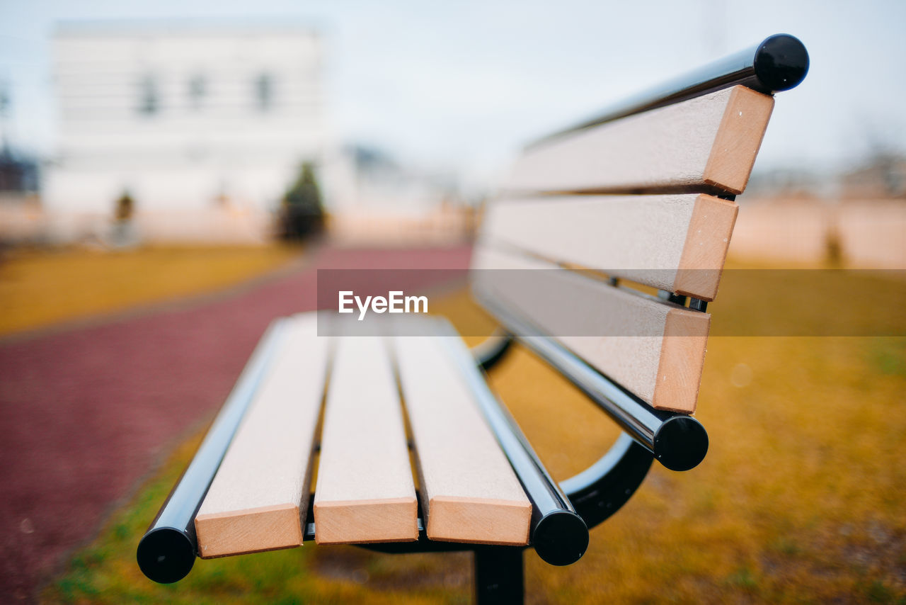 focus on foreground, day, no people, close-up, nature, wood - material, absence, outdoors, table, metal, selective focus, park, land, security, field, park - man made space, still life, protection, relaxation
