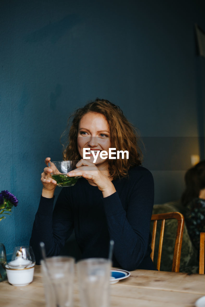 Smiling Woman Holding Herbal Tea While Sitting At Cafe