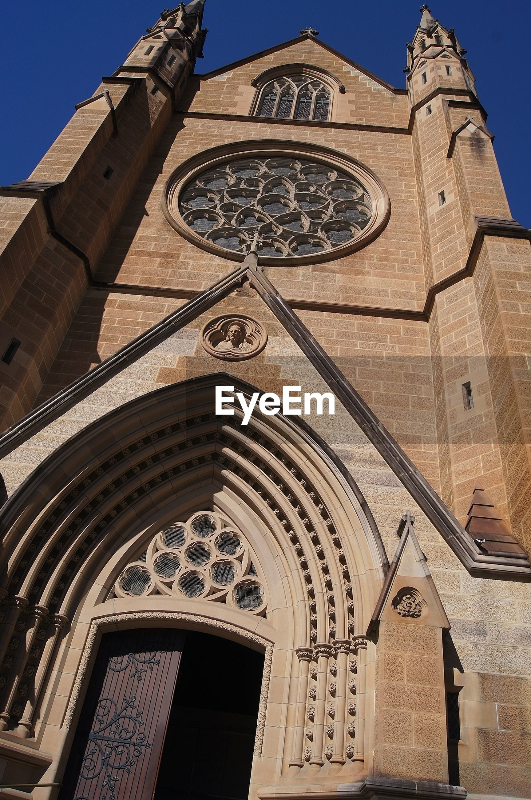 architecture, building exterior, low angle view, built structure, church, religion, clear sky, place of worship, spirituality, blue, history, facade, ornate, day, cross, arch, window, outdoors