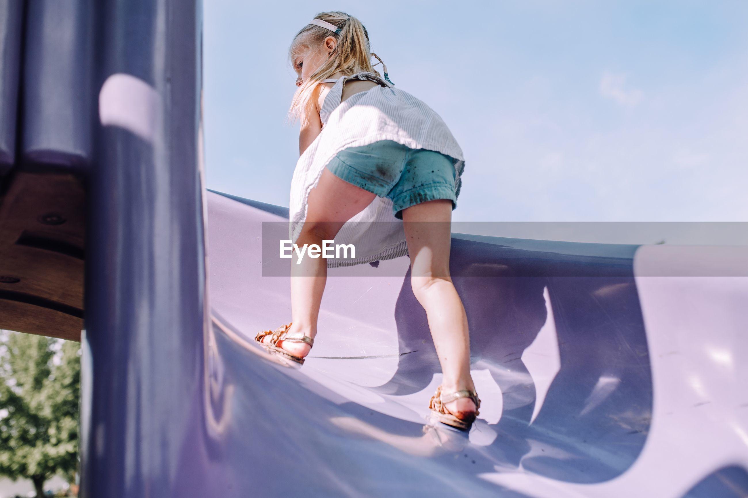 Full length of girl playing on slide against sky