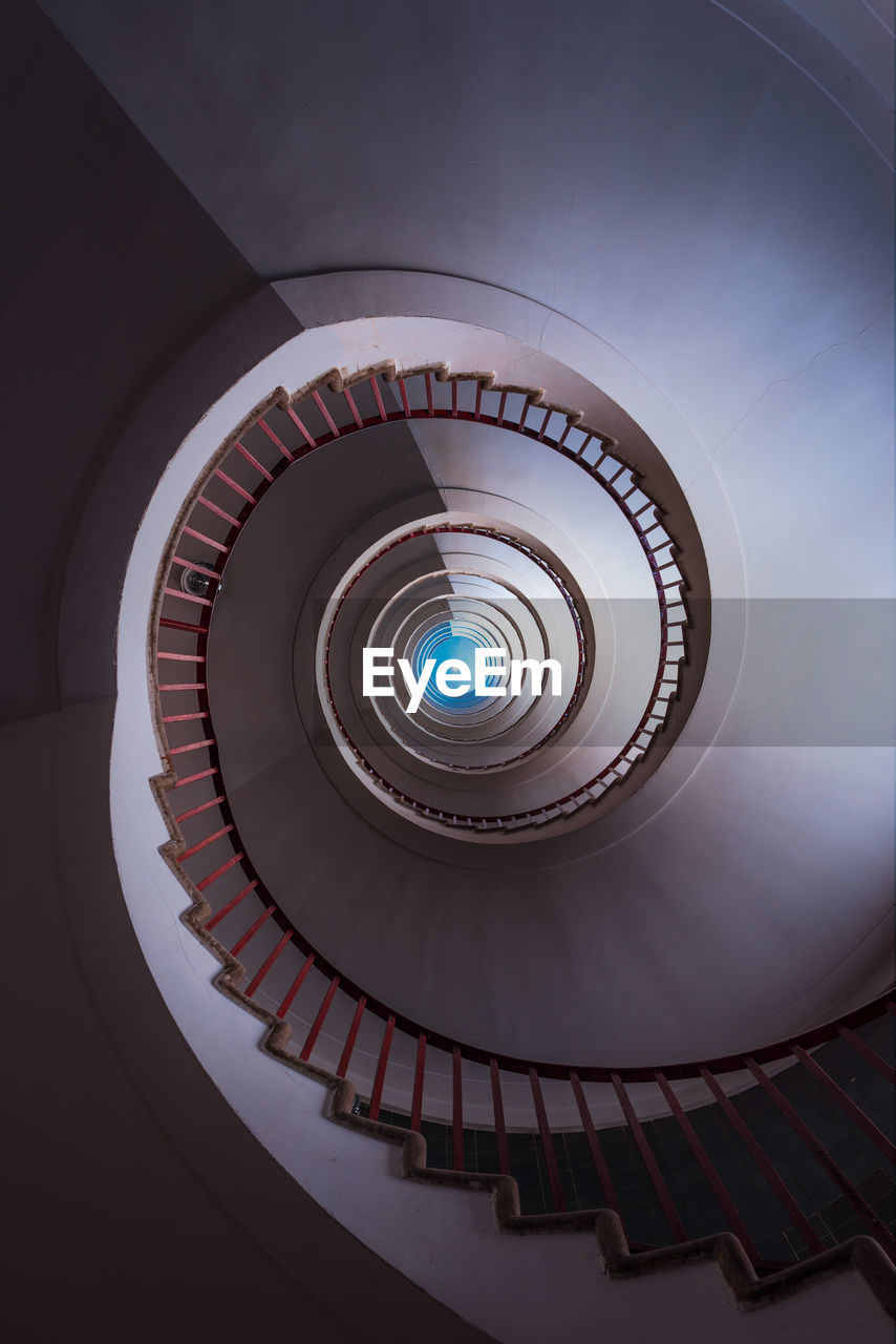 spiral, steps and staircases, architecture, staircase, built structure, railing, indoors, spiral staircase, low angle view, directly below, pattern, no people, shape, geometric shape, design, circle, building, diminishing perspective, ceiling, day, light at the end of the tunnel