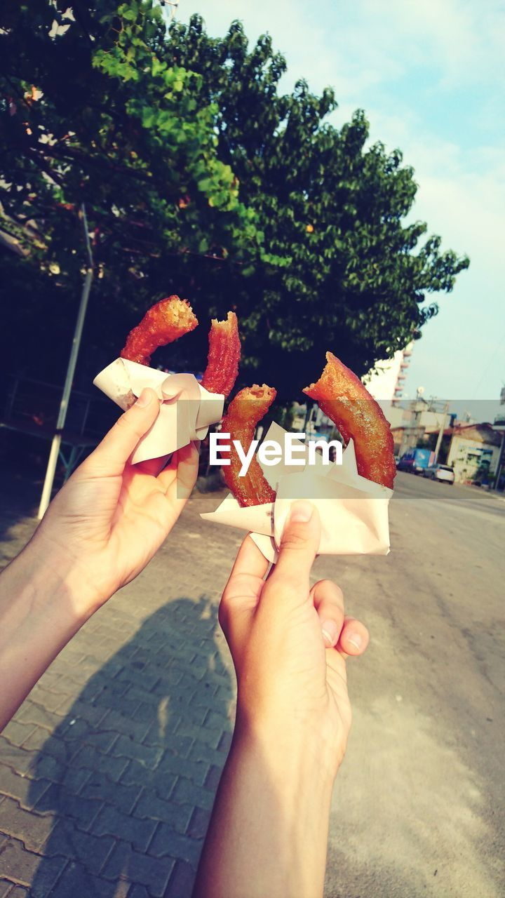 human hand, human body part, real people, personal perspective, one person, holding, food and drink, leisure activity, food, lifestyles, outdoors, close-up, day, women, sweet food, freshness, friendship, nature, ready-to-eat, sky, people
