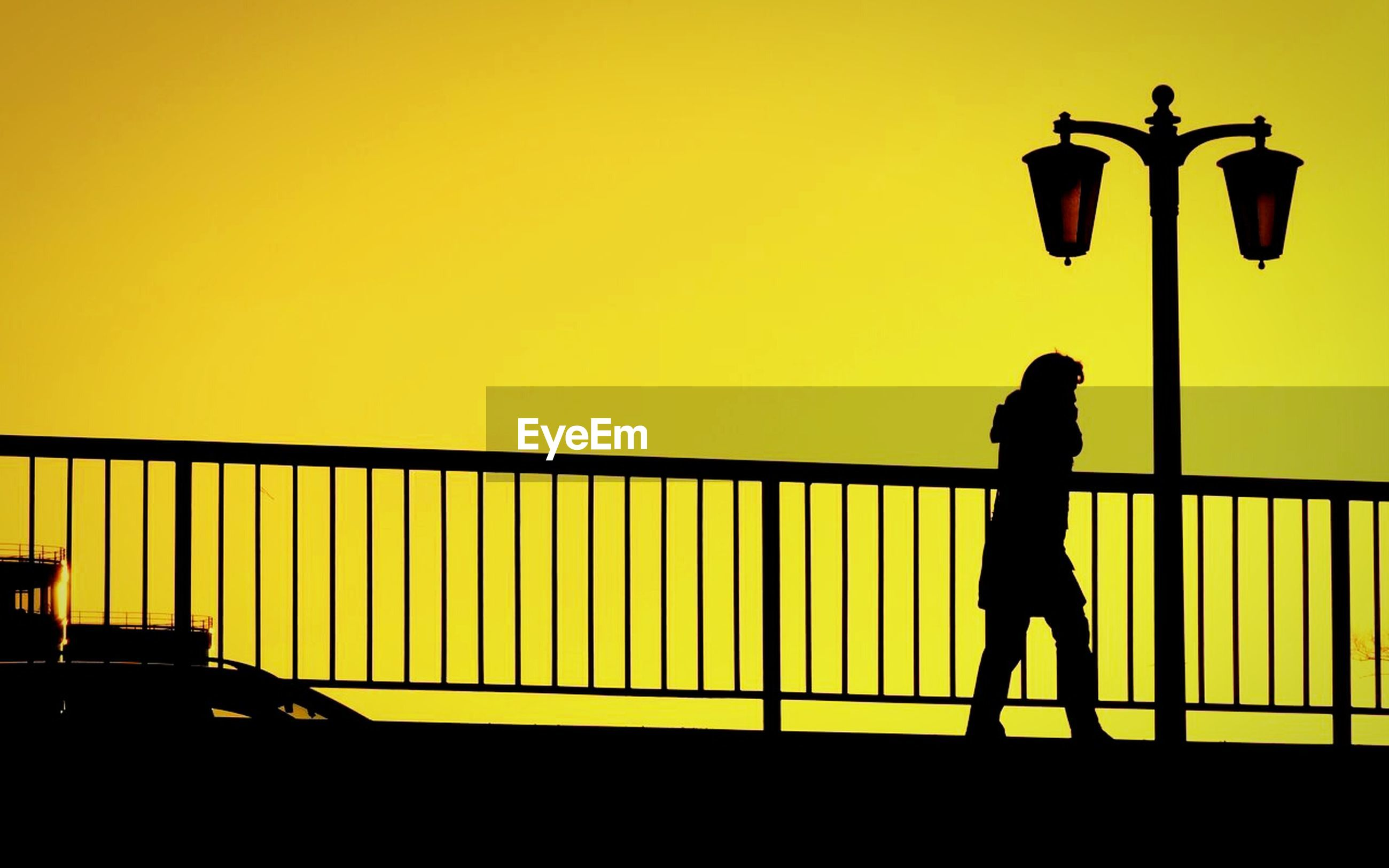 Side view of silhouette person walking on bridge against clear yellow sky