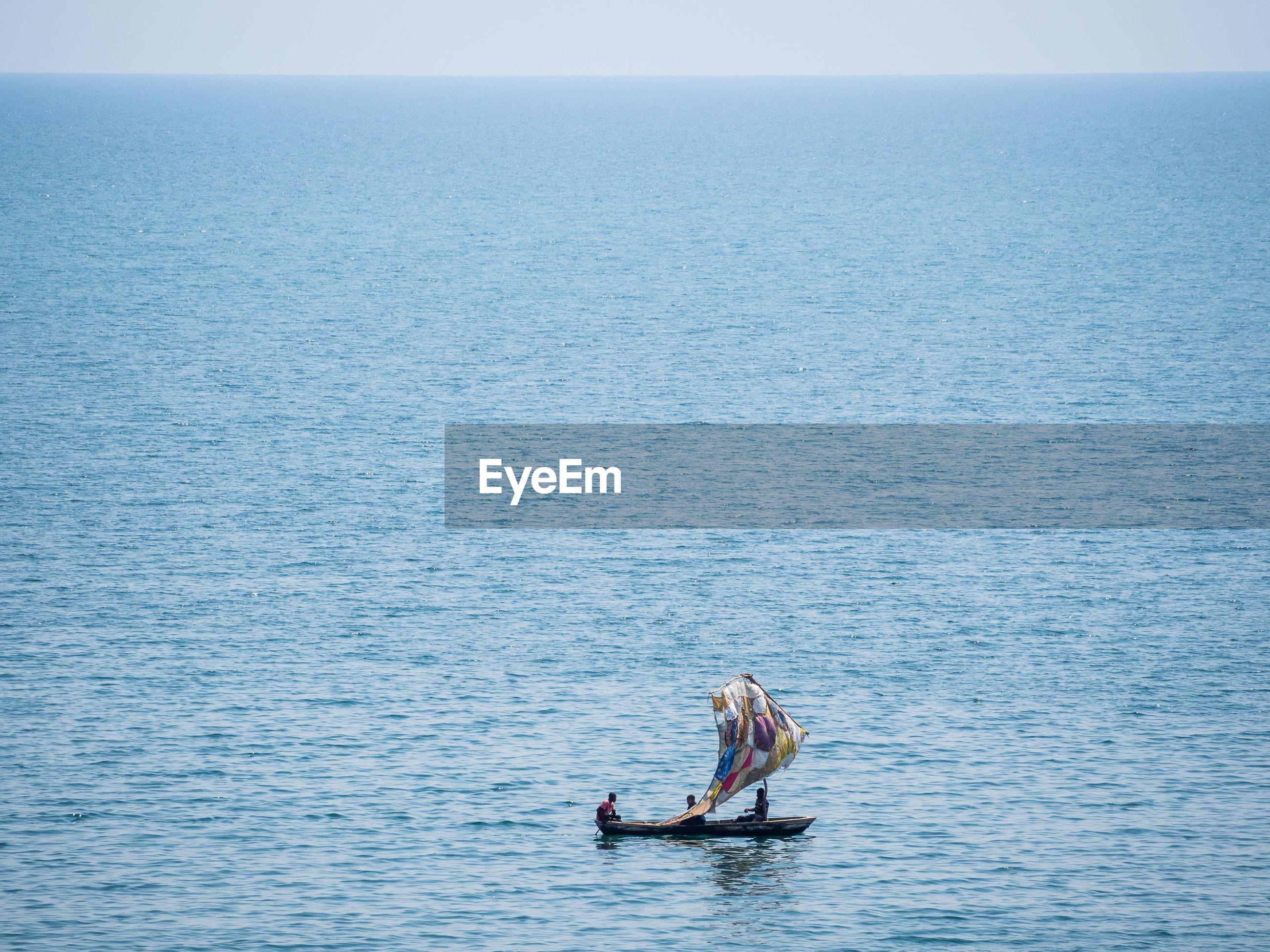 People in simple sailing boat on lake tanganyika against sky, zambia