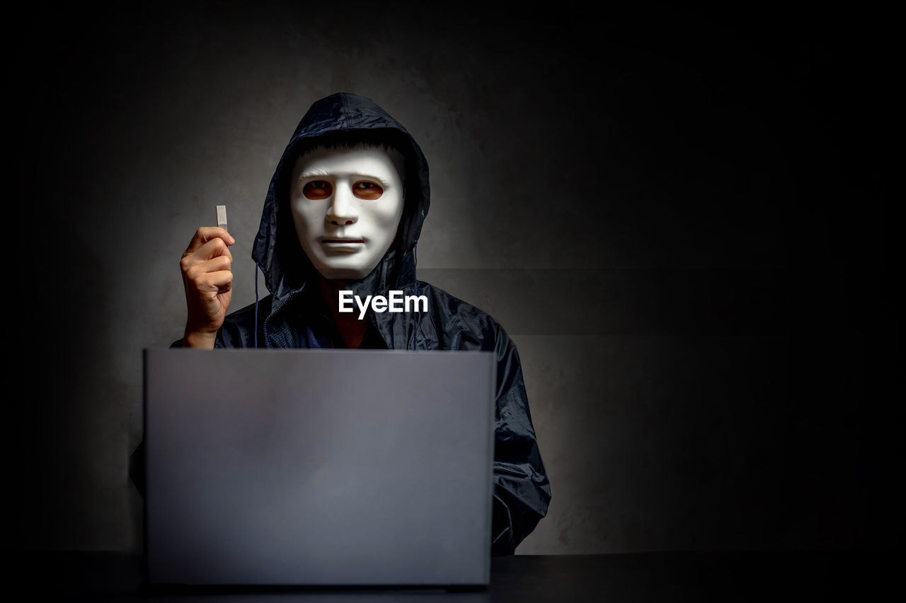 communication, one person, front view, indoors, laptop, using laptop, studio shot, spooky, computer, portrait, copy space, technology, wireless technology, dark, looking at camera, adult, disguise, black background, sign, aggression, evil, hood - clothing