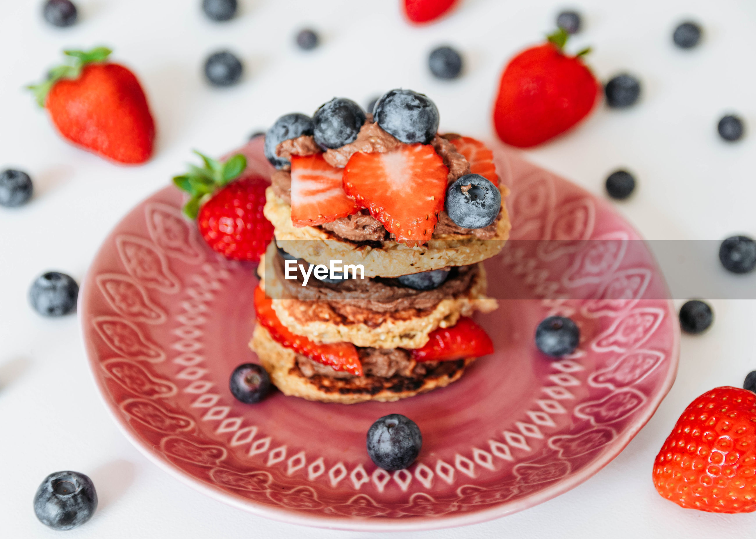 Banana and oat pancakes with chocolate cream, strawberries and blueberries.