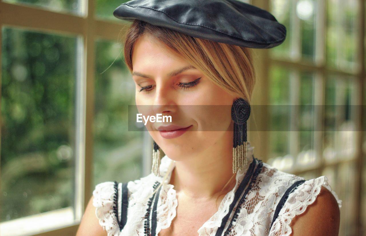 Beautiful young woman wearing hat by window