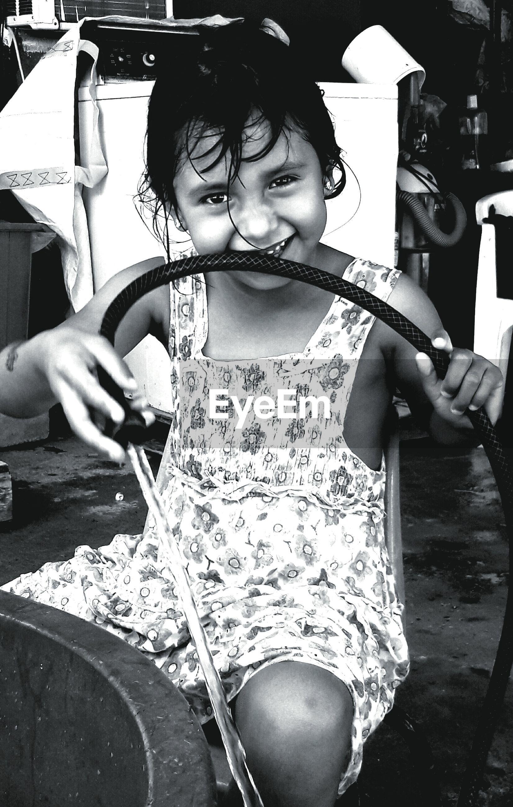 Portrait of smiling girl holding garden hose