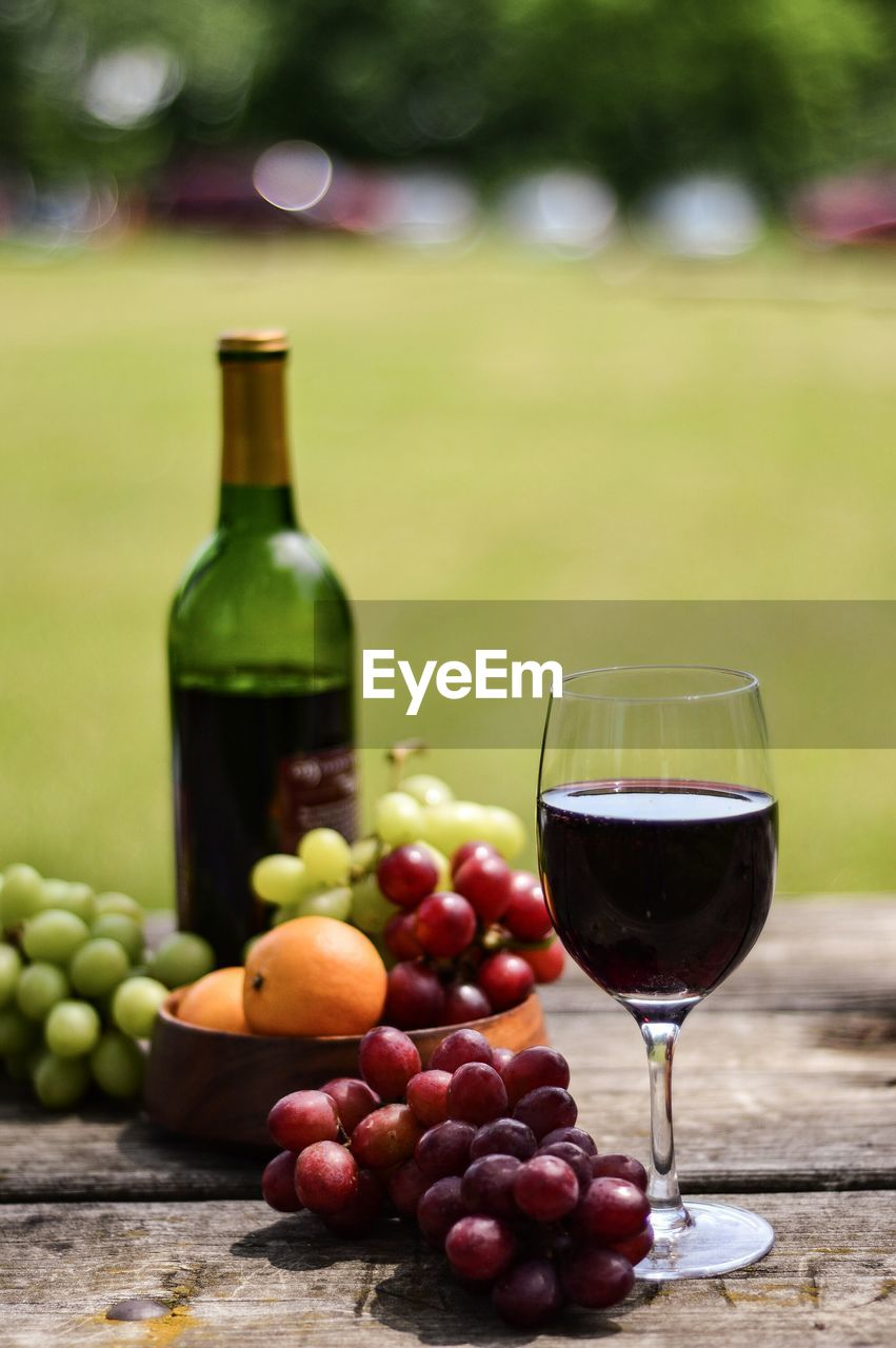 Close-up of red wine and grapes on table