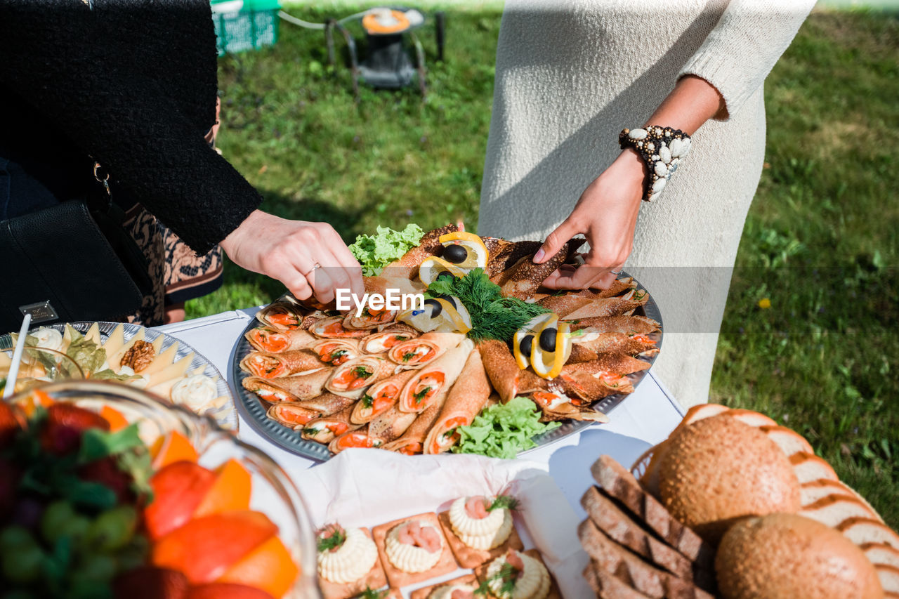 Midsection of women having food in yard