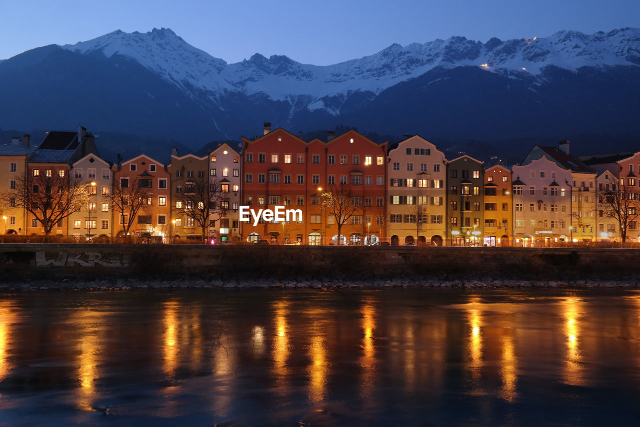 Illuminated Buildings By River Against Mountain During Winter In Town At Dusk