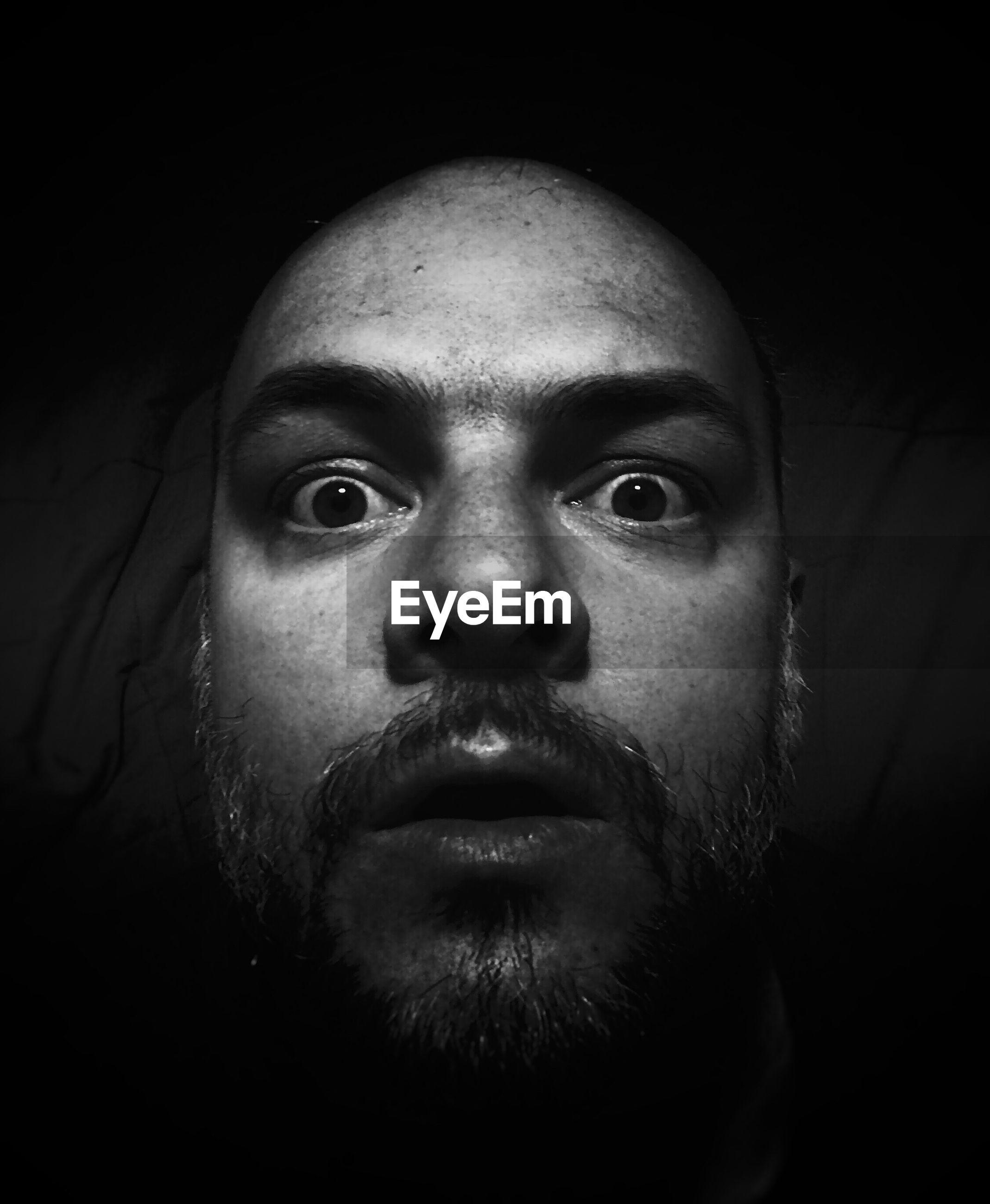 Close-up portrait of surprised man in dark room